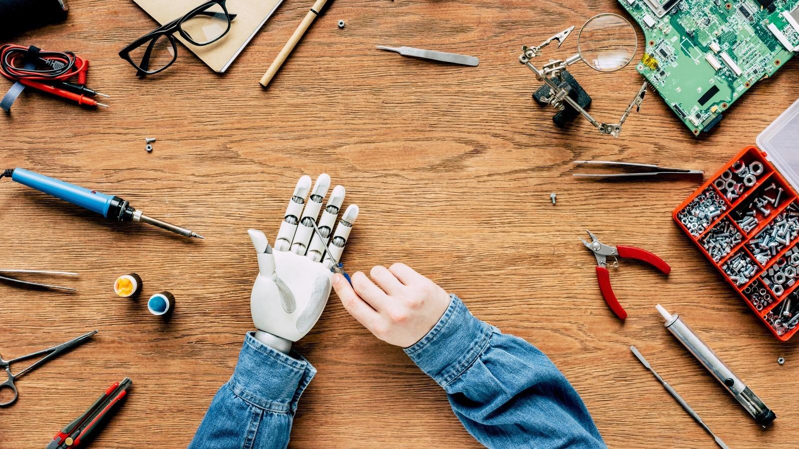 man-fixing-robotic-hand-by-screwdriver.jpg